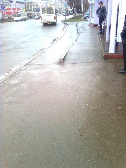 Пандус сделан от бордюра к проезжей части дорогм, а с платформы, на которой стоит остановочный комплекс. Он образует своеобразную ступеньку в метр шириной. Это абсолютно бессмысленный пандус. Он не делает достпуным подъезд колясочника к общественному тран
