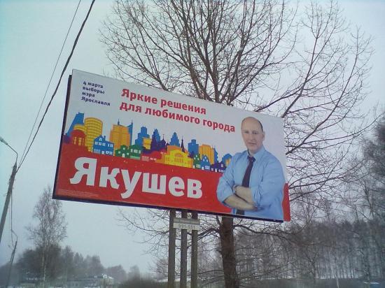 Та-а-дам! А вот и он. Яков Якушев. С засученными рукавами на фоне разноцветного мультяшного города. Тут бы пухлый блатов смотрелся гораздо лучше. Такой бы был