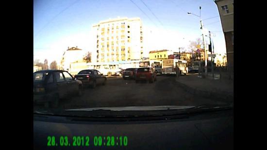 С привокзальной площади на улицу Мира на зелёный сигнал светофора движутся в правой полосе троллейбус, 2 автобуса и красный форд, в левой полосе - автобус ПАЗ, чёрный Логан, чёрный Ланос и др.
