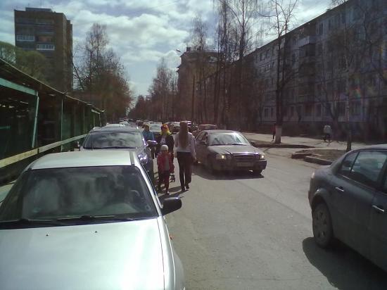 люди идут по дороге, кругом машины.